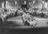"VE-Day party for the children of North Town, ready for their tea in St. Augustine's Church Hall. The tables are arranged in a ""V for Victory"", and at the back is the Mayor with the party organisers."